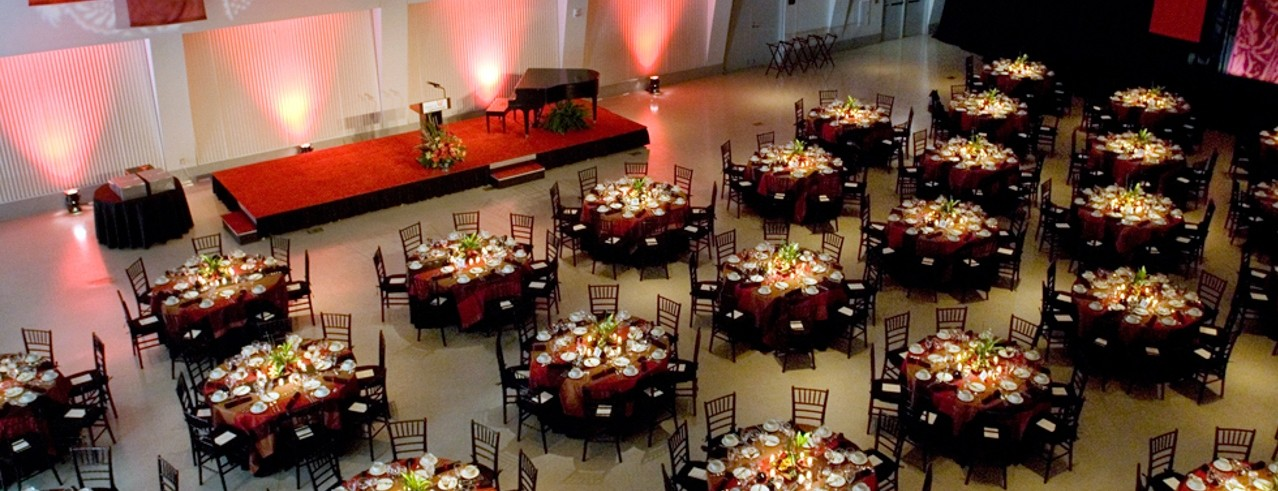 Round tables with formal dinner settings and chairs in Tangemann University Center Great Hall.