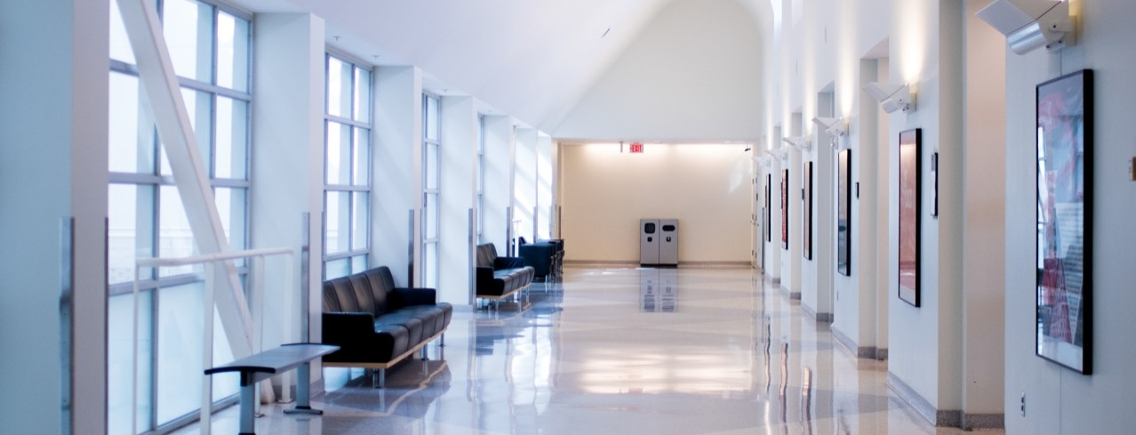 A long hallway with bright lighting and several benches