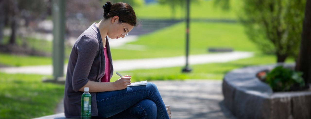 a student sitting outside and writing in a notebook