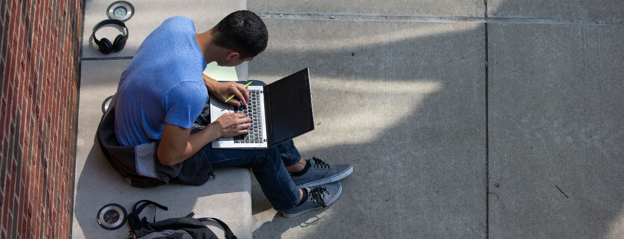 A student works on a laptop on UC's campus