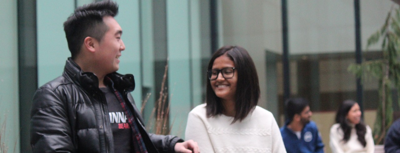 Two international students talk to each other in the Lindner College of Business courtyard.