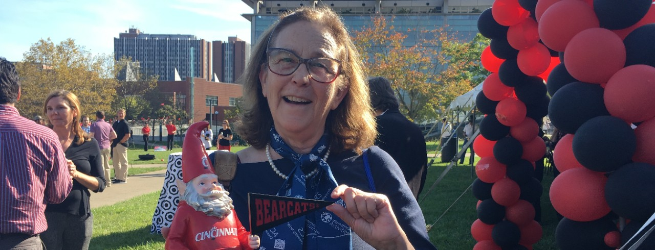 A UC professor shows off a Cincinnati-themed gnome at UC's homecoming celebrations.