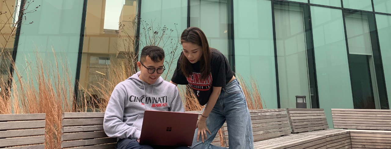International students cheer on the Bearcats at a football game.