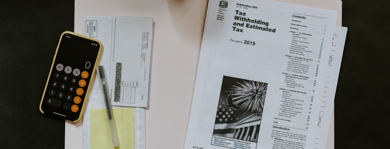 Tax forms and a calculator lay on a manila folder.