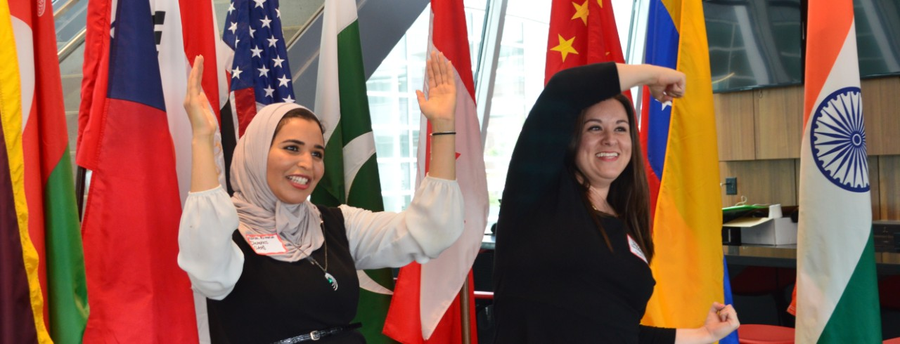 Two women form the letters UC with their arms, standing in front of flags from a variety of countries.