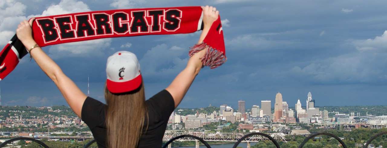 Female wearing UC hat, holding up Bearcats scarf with city skyline in background.