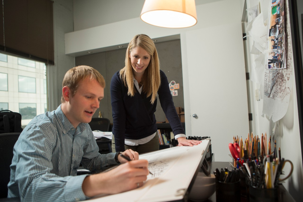 Two people working in office on design project