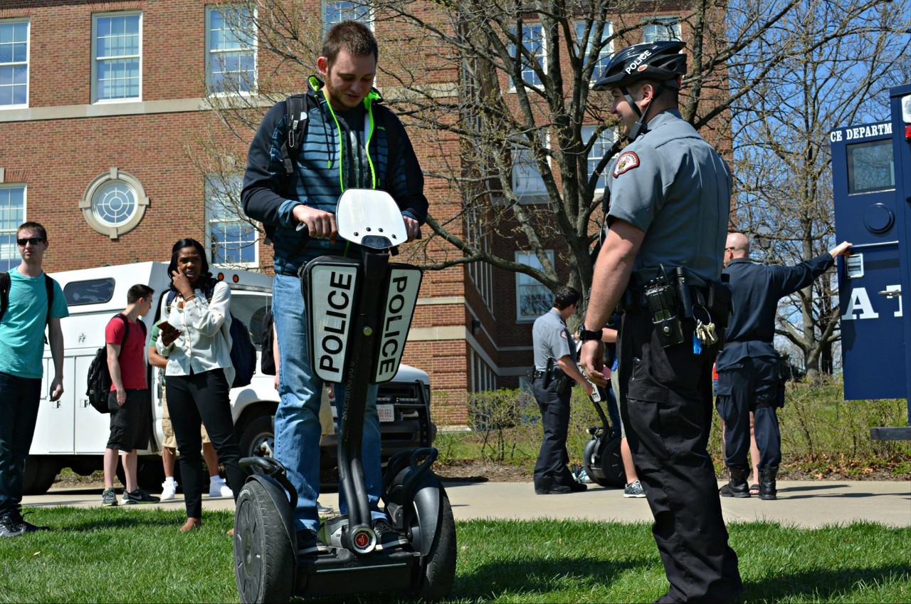 An officer teaches a student to ride a segway.