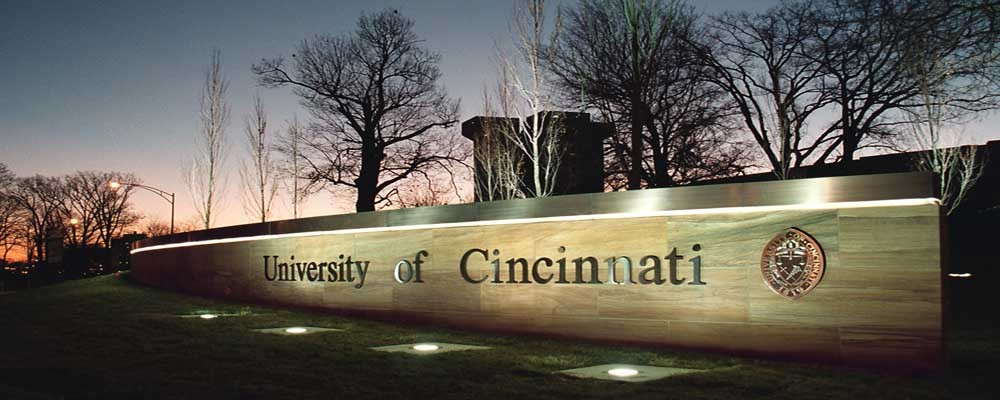 The University of Cincinnati sign is lit up at dusk by lights.