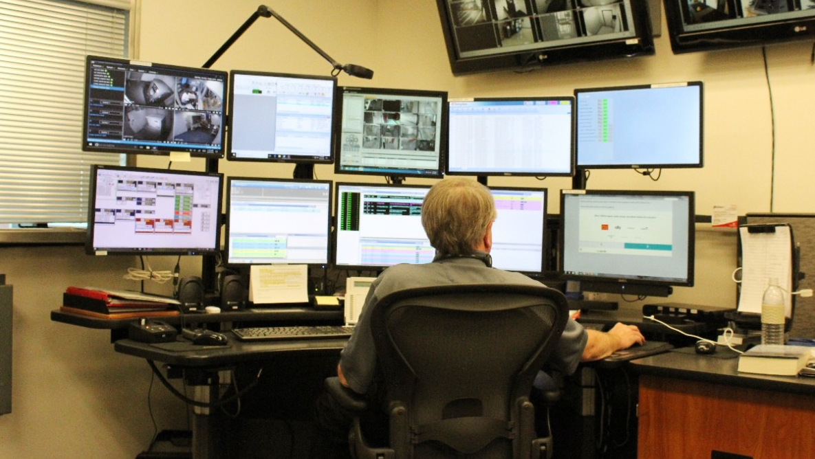 A dispatcher monitors multiple screens in UC's 911 Communications Center.