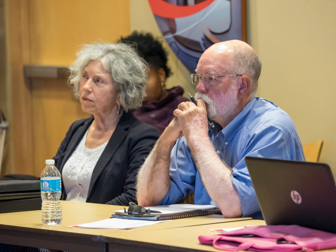Two members of the Community Advisory Council listen attentively during a meeting.
