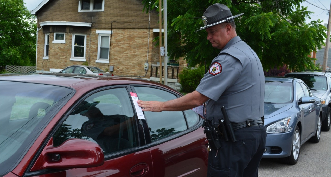 A UCPD officer puts a flier with theft from auto safety tips on a car.