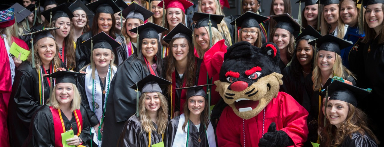 The Bearcat poses in his graduation cap and gown with other students at graduation.