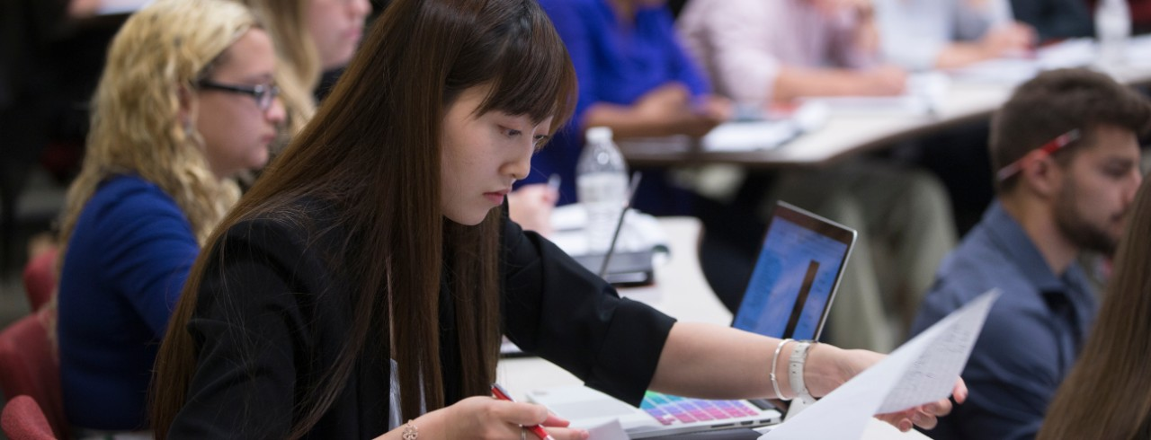 A Student works looks through notes in a notebok in a lecture hall