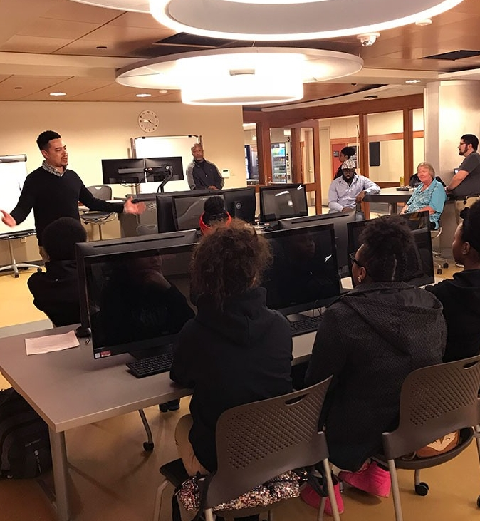 Students seated in a computer lab listening to an instructor in Share IT.