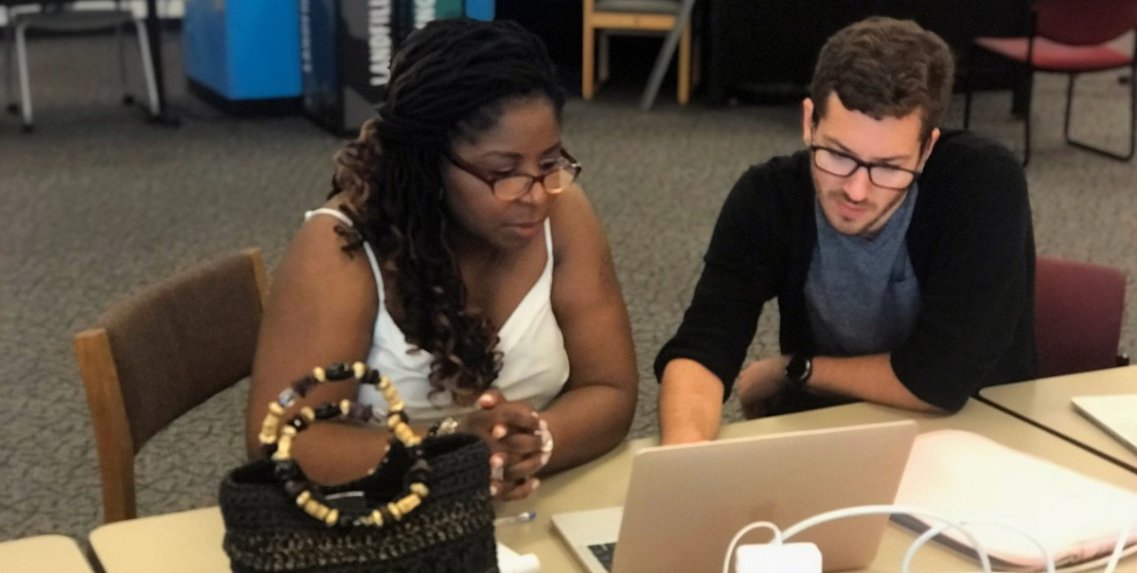 Instructional technologist works with faculty member on her computer