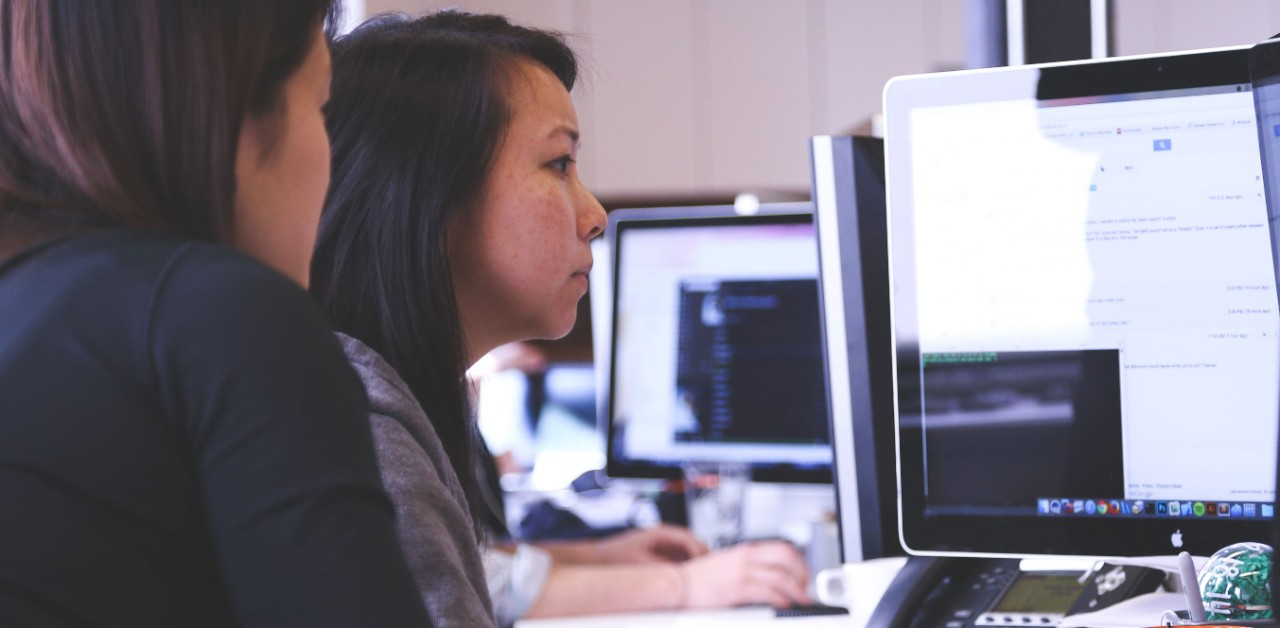 two women working at a computer screen collaboratively