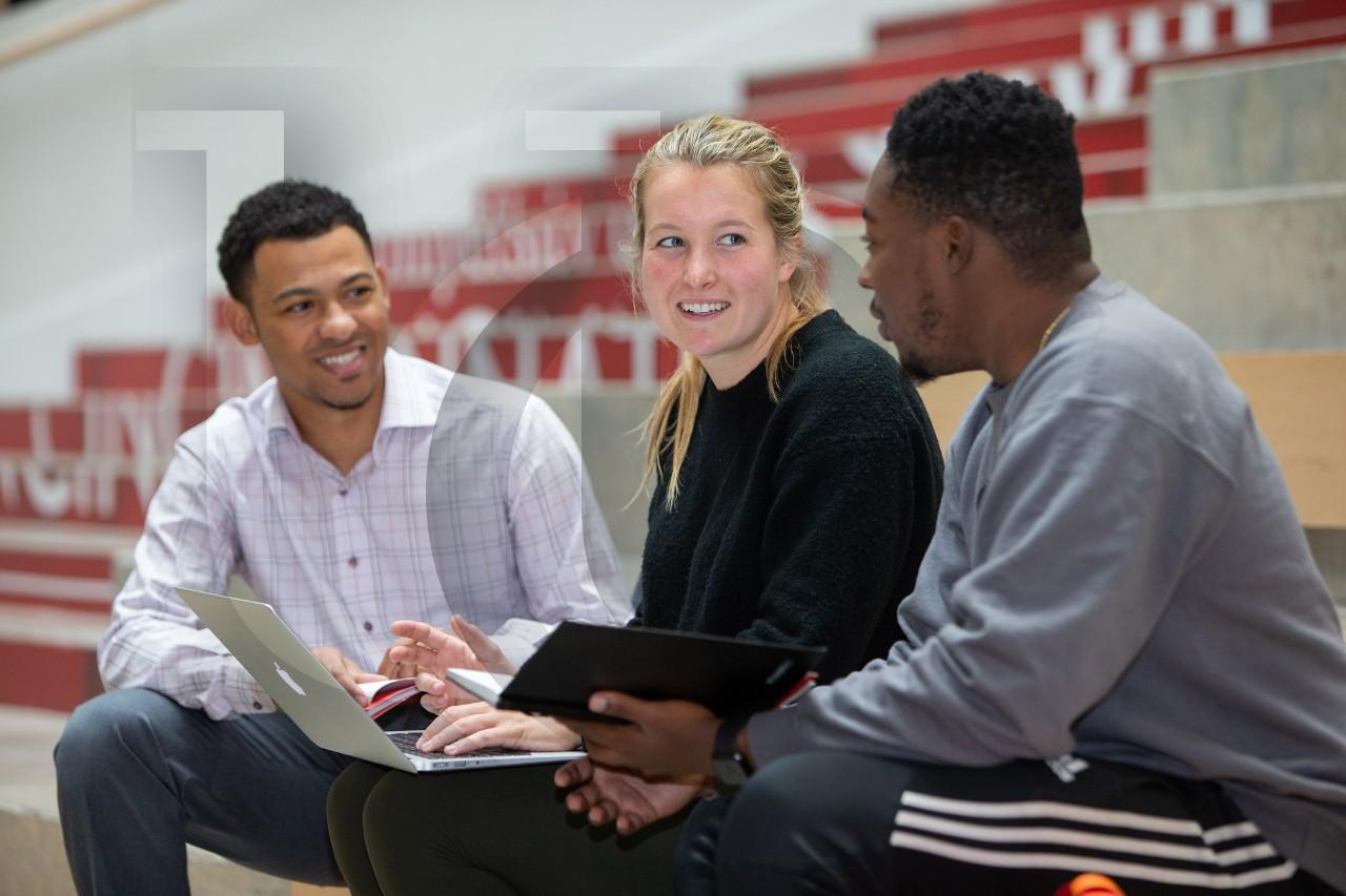University of Cincinnati students converse on the steps in Lindner Hall