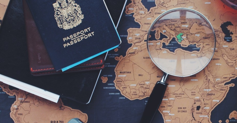 A passport, travel documents, and map with a magnifying glass
