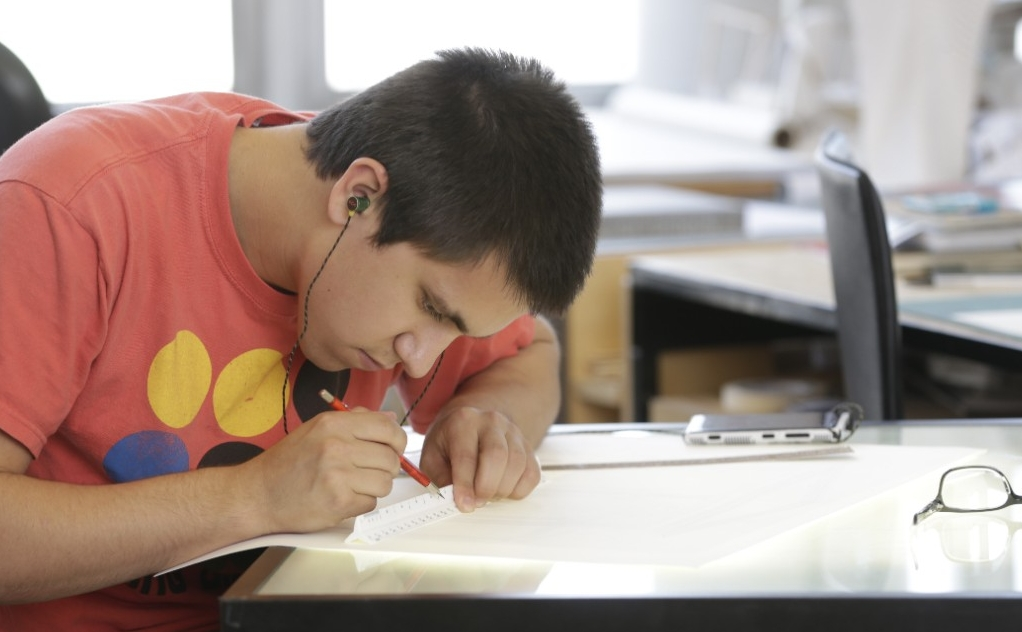Student works at a drafting table