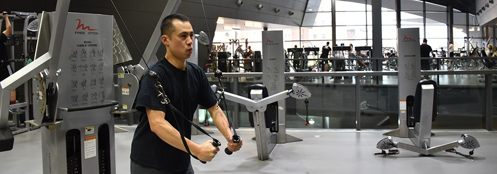 A guest uses the weights at the Campus Recreation Center.