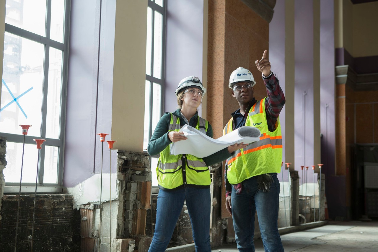 Student and manager in safety vests on a construction site looking at plans and pointing.