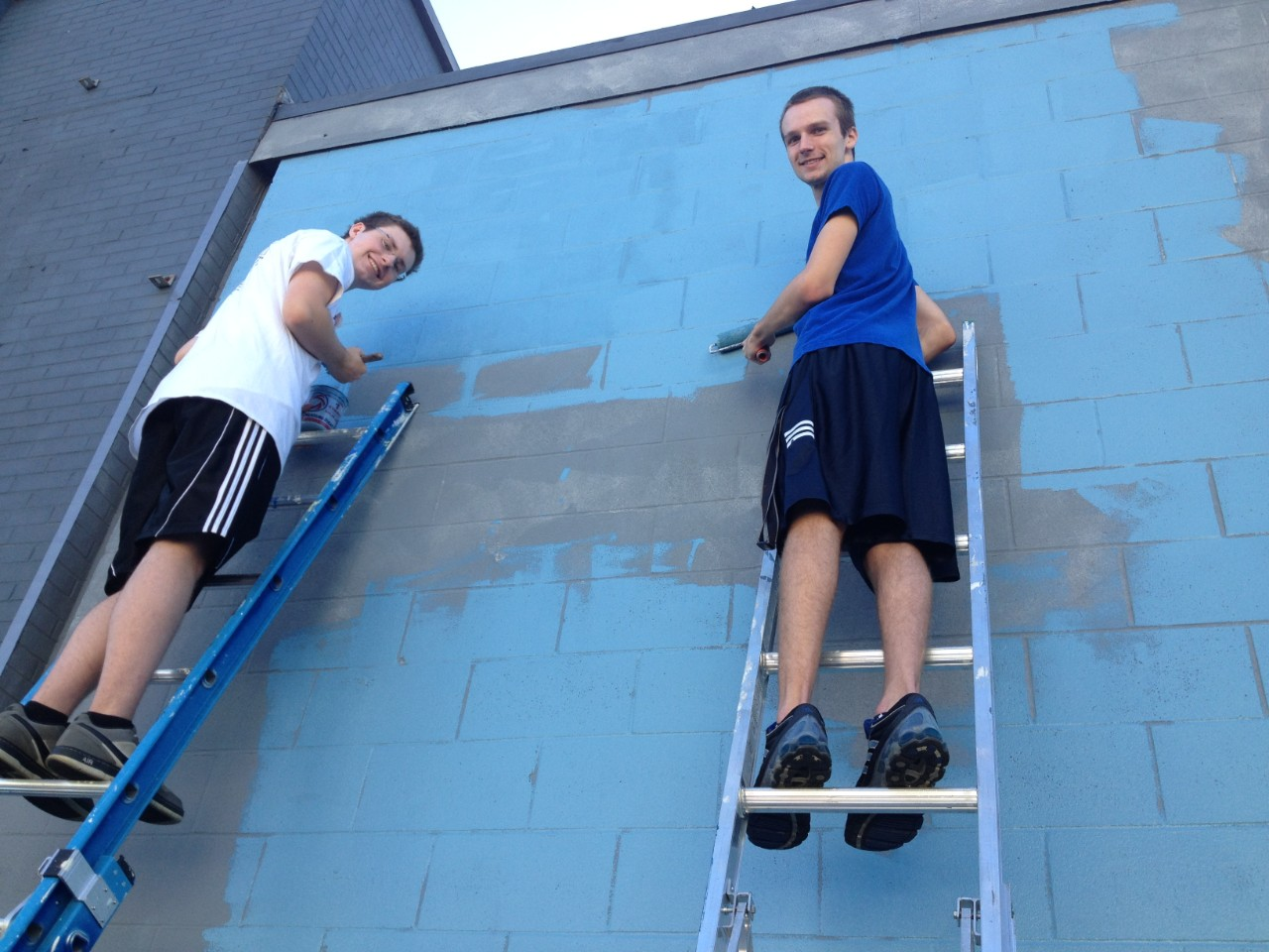 Students painting the outside of a building during Into the Streets