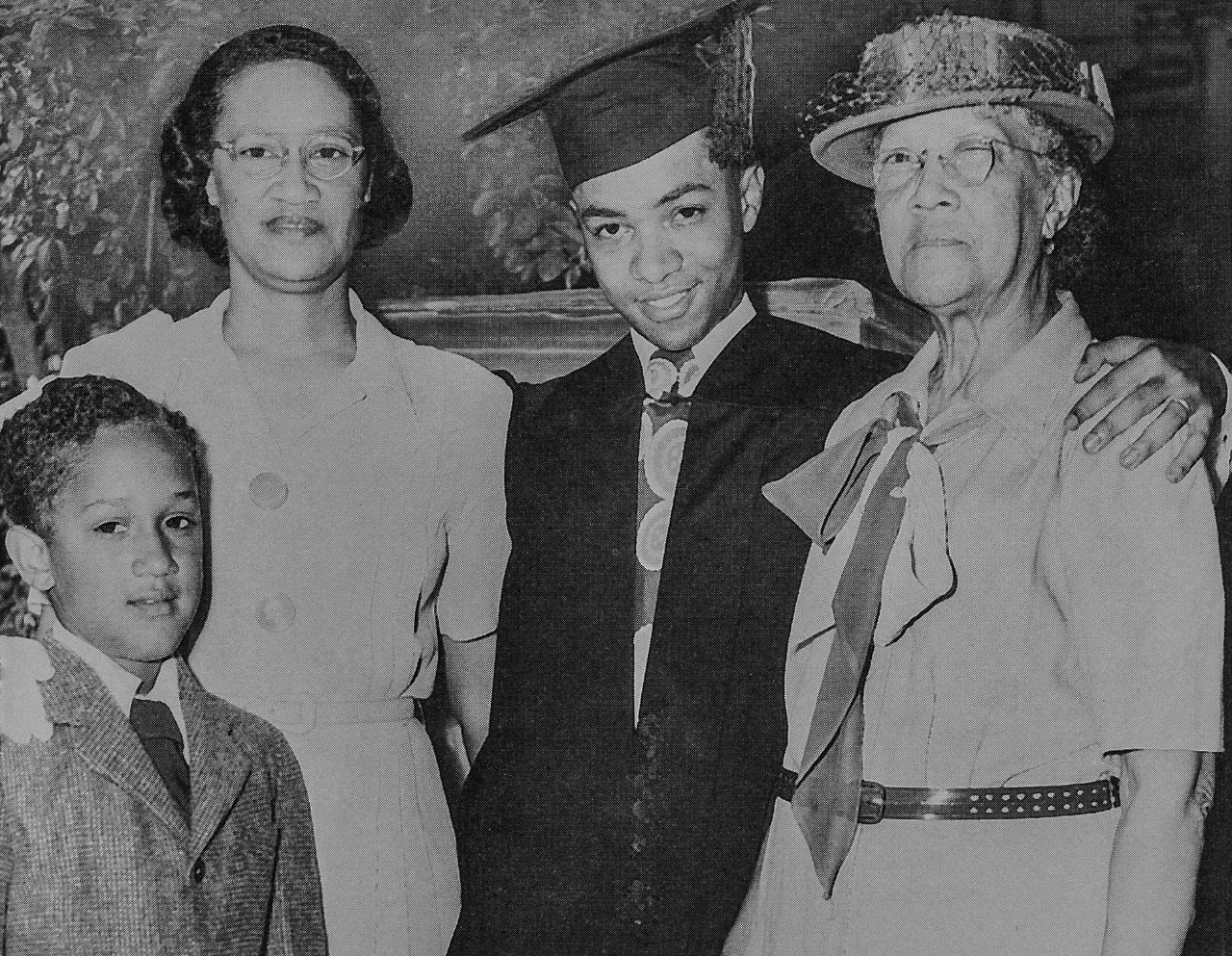 Photo of Darwin T. Turner with his family graduating from the University of Cincinnati with his bachelor's degree at age 16 in 1947.  Darwin T. Turner is featured in the middle with his cap and gown.