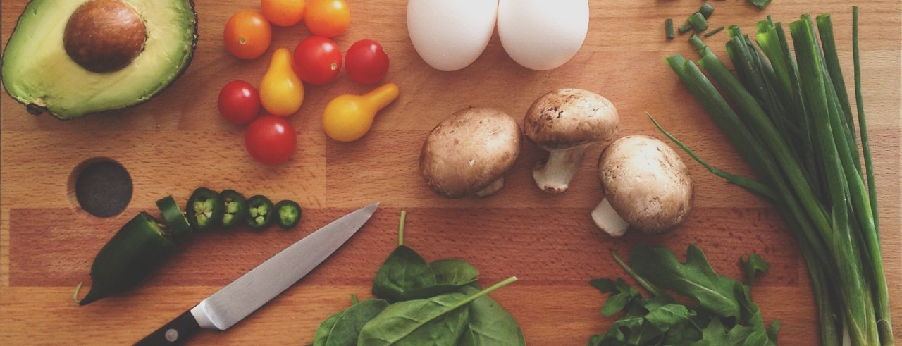 Vegetables, eggs and a knife laid out on a wood cutting board