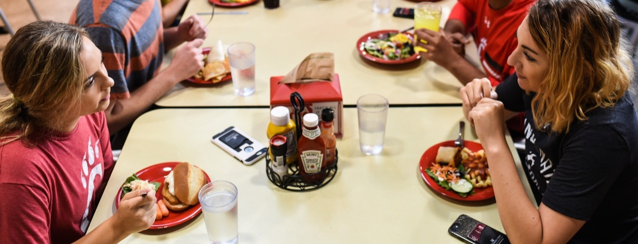 Students sit at a long rectangular table eating and chatting in a University of Cincinnati dining center.