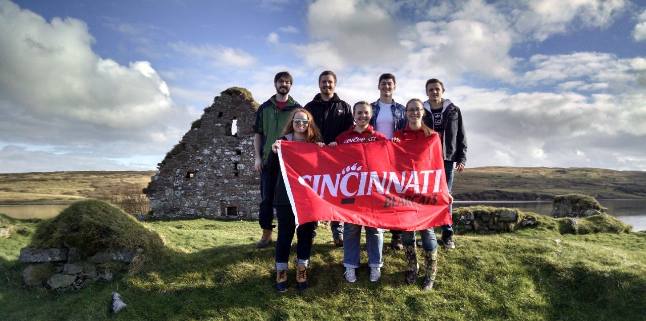 Honors students holding a UC banner in front of ancient ruins