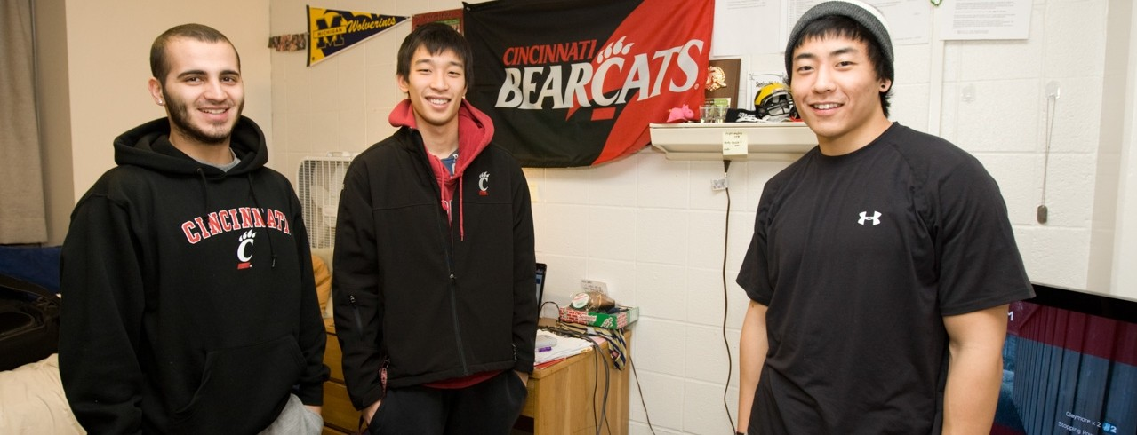 The student roomates stand in their room smiling.