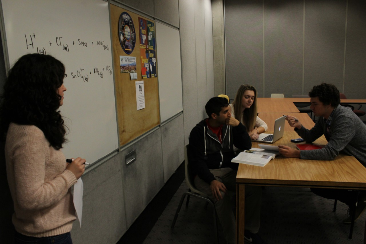 A group of University of Cincinnati students looking up at a student writing on a whiteboard in the Learning Commons