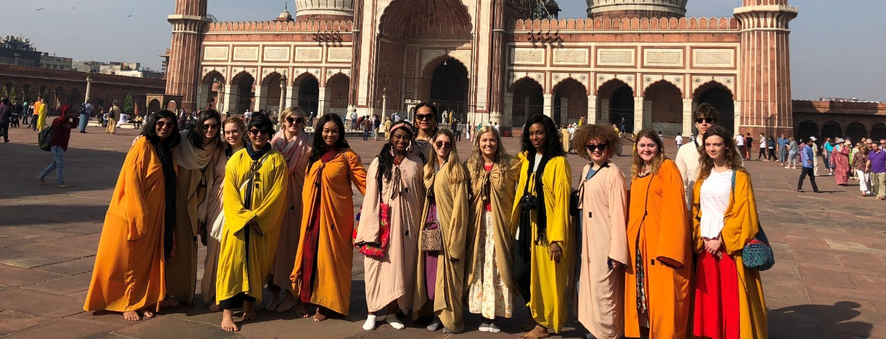 Students in colorful traditional Indian clothes stand in front of a temple.