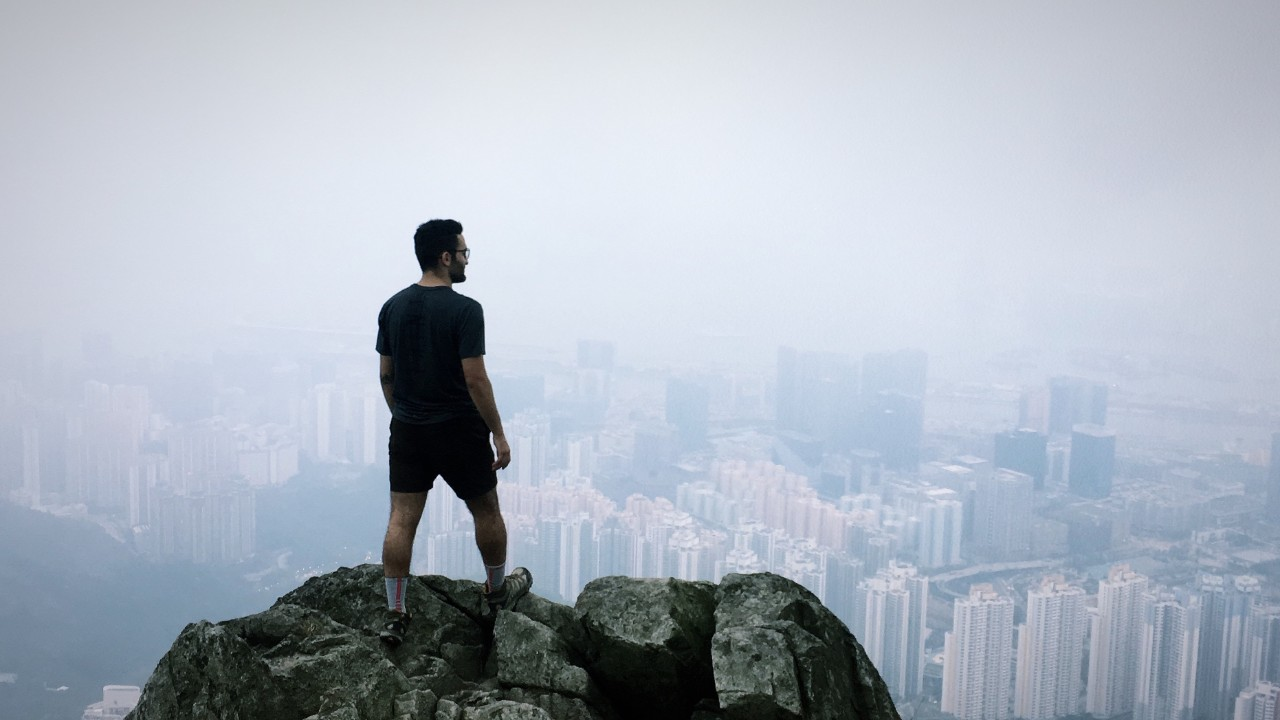 Student stands above the Hong Kong skyline in fog.