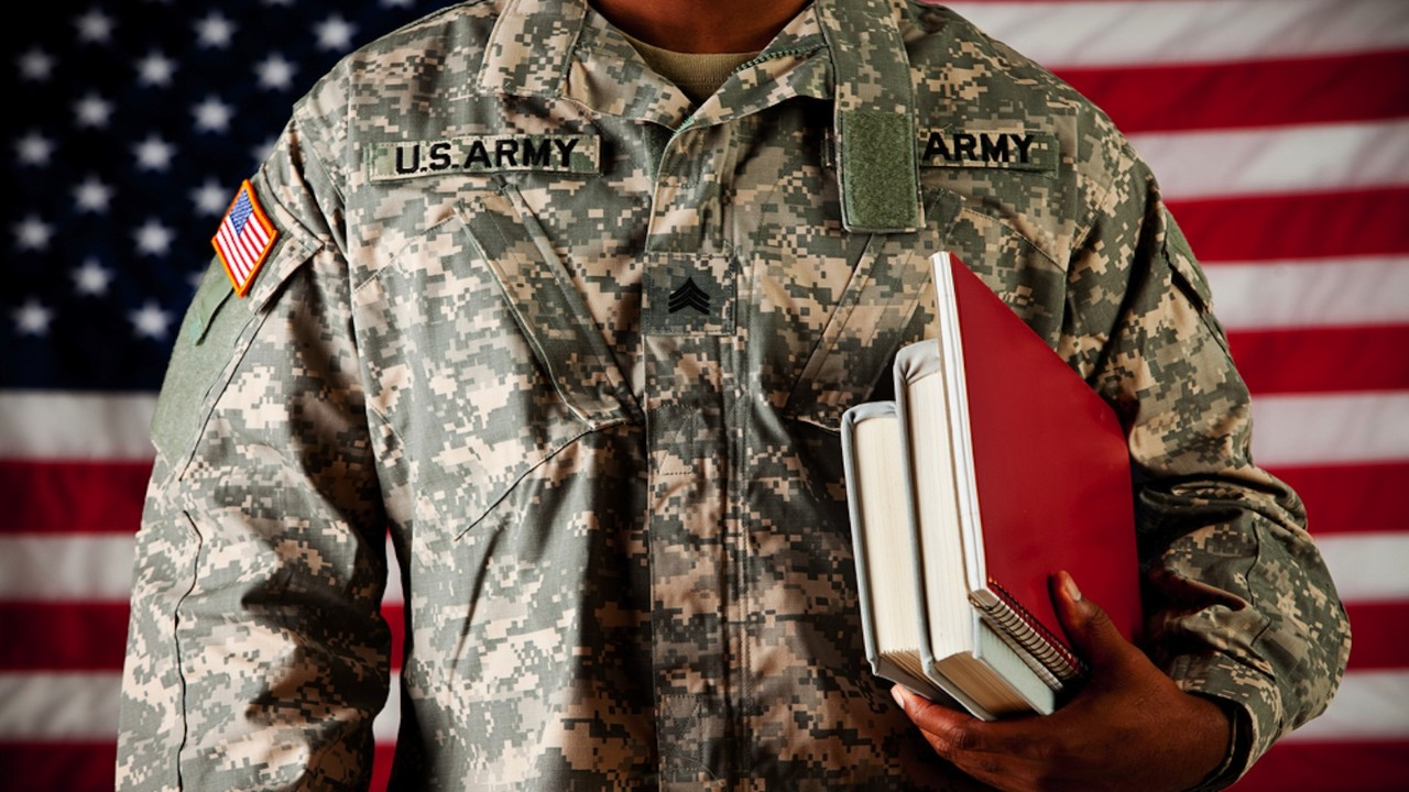 Soldier holding books in front of American Flag