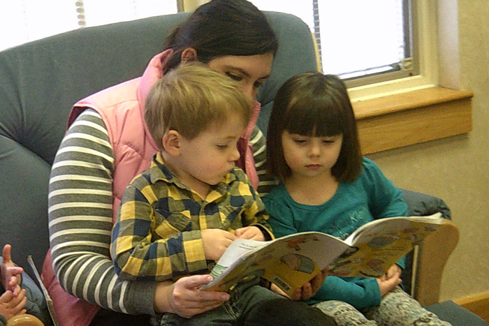 A volunteer in a rocking chair reads to toddlers