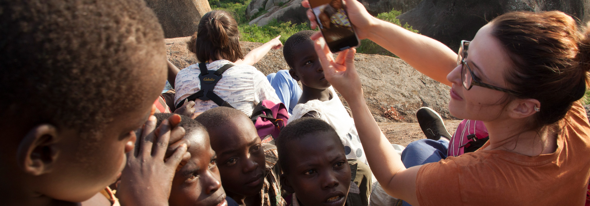 Pharmacy student Lauren Stacey shares photos with local children on a hike in Tanzania