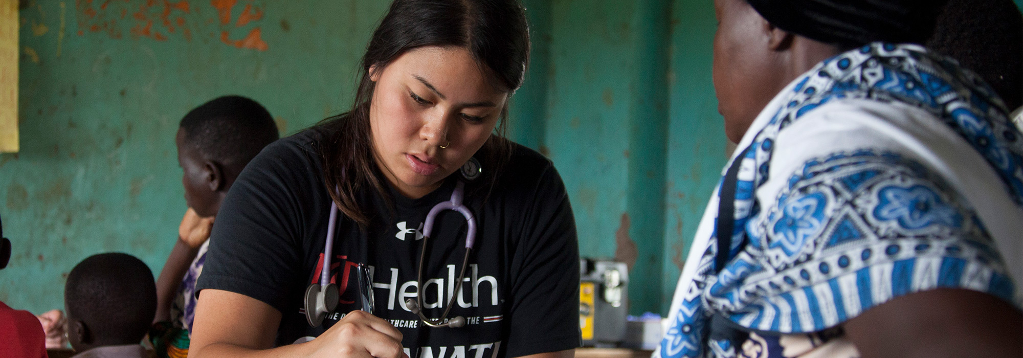 Nursing student Sabrina Bernardo helps a patient in a free clinic in Tanzania