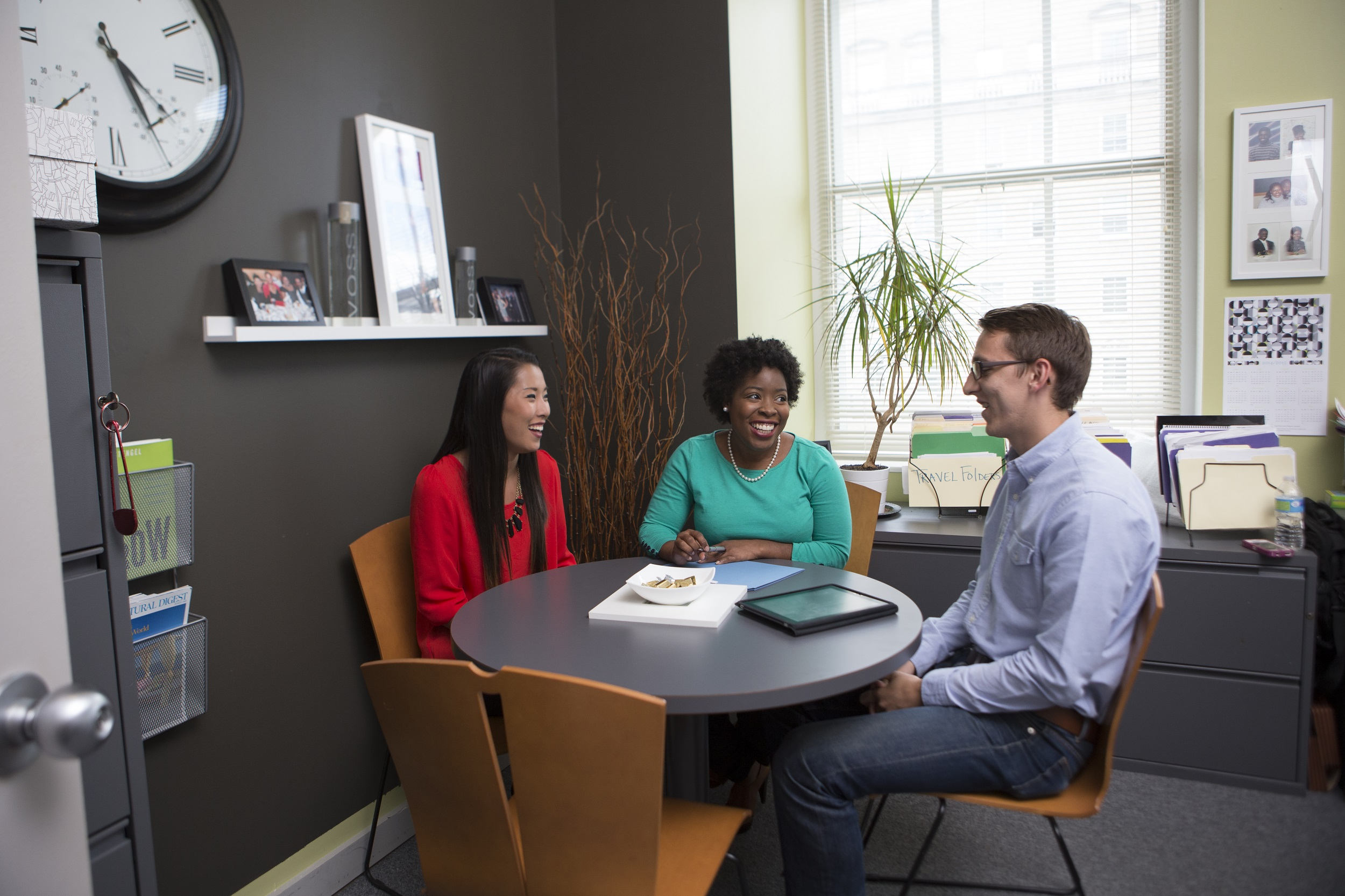 Three people sitting at a round table in an office.
