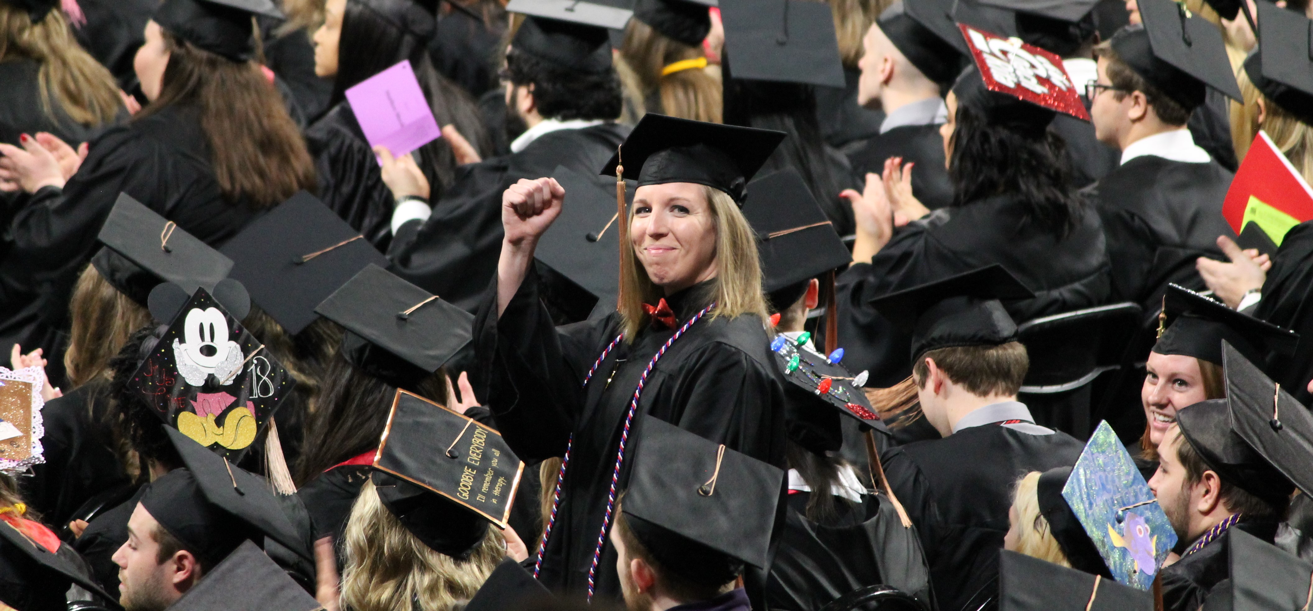 Graduate raising hand in celebration in crowd of fellow graduates at Commencement Ceremony.