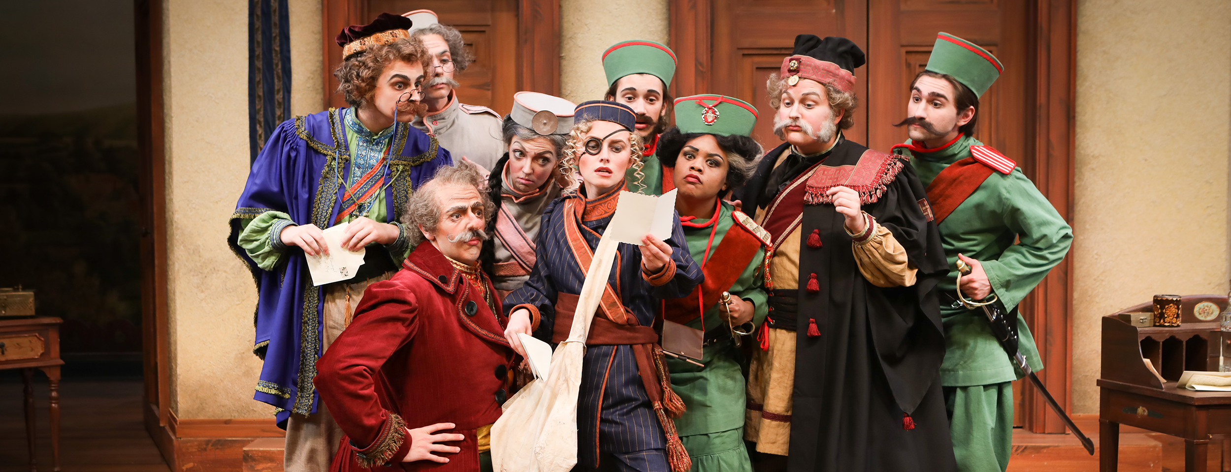 "Actors in character gathered around a mailed letter in CCM's production of ""The Government Inspector."""
