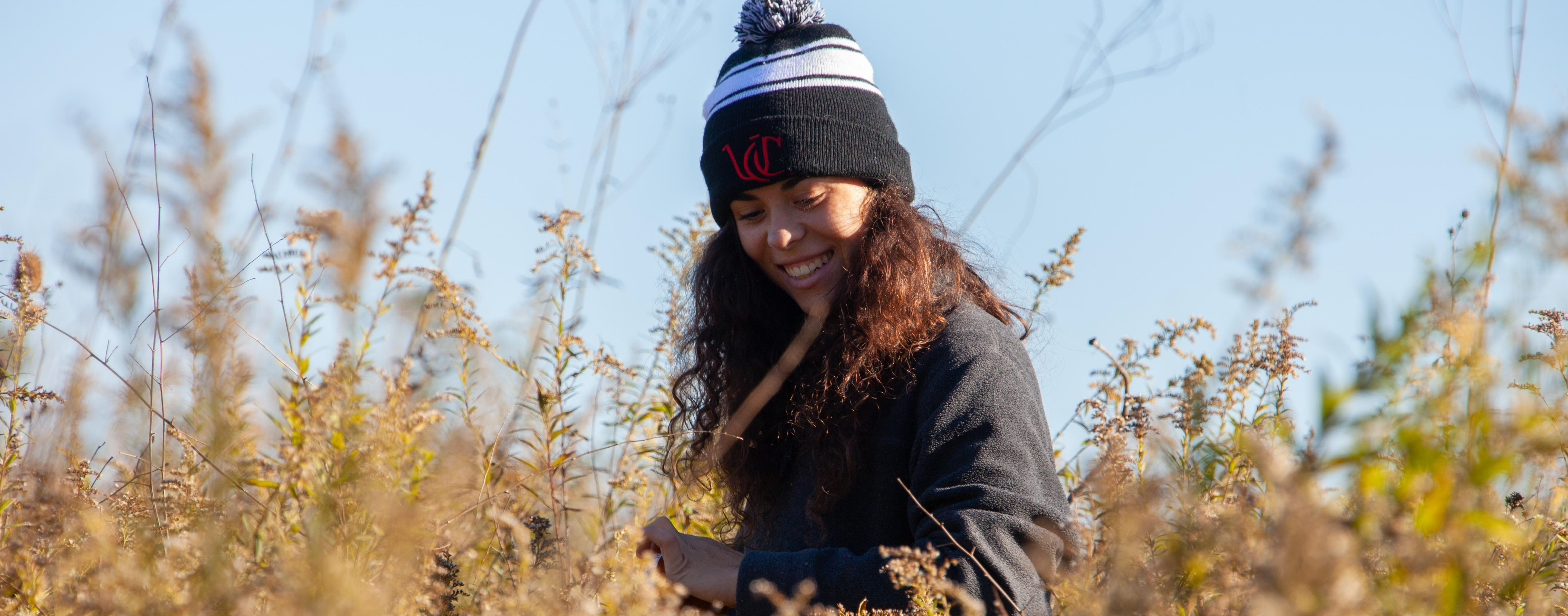 A UC botany student wearing a UC knit cap smiles in a field of yellow goldenrod.