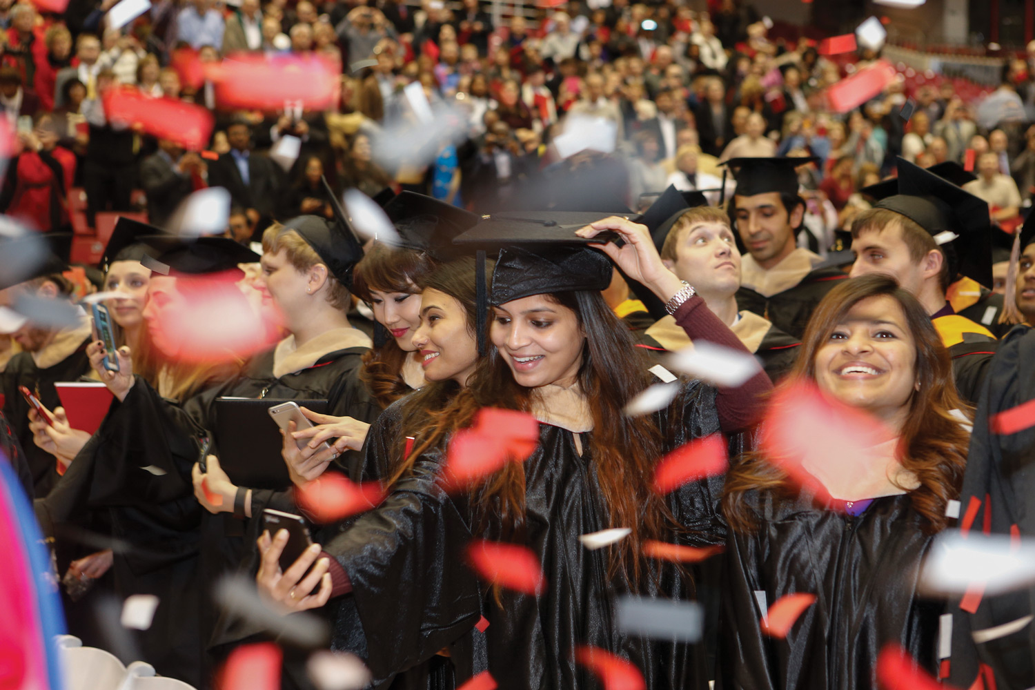 A student takes a selfie at hooding ceremony