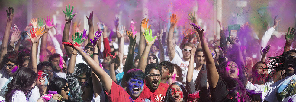 Students celebrating Holi festival by throwing color into the air.