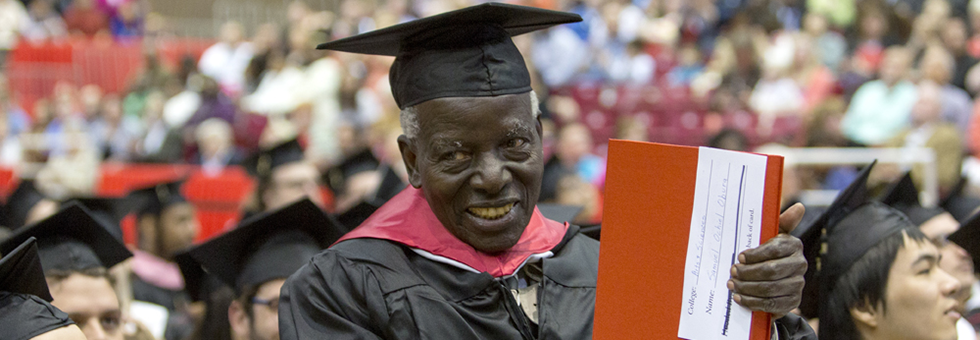 Samuel Ochiel Obura stands to be recognized at commencement ceremony.