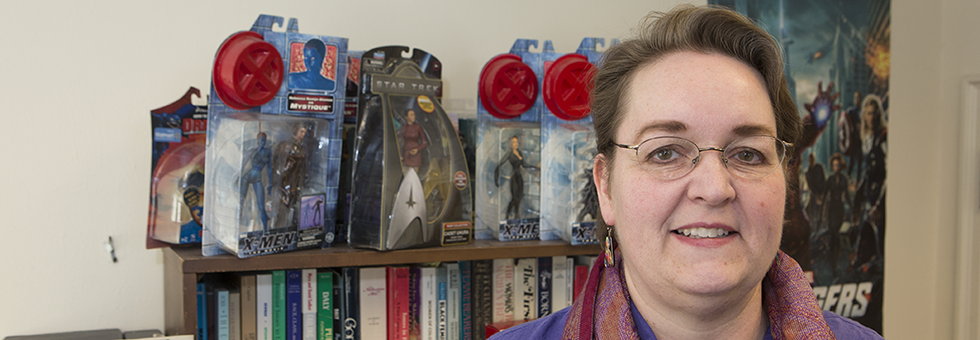 Rebecca Borah stands in front of a collection of super hero action figures.