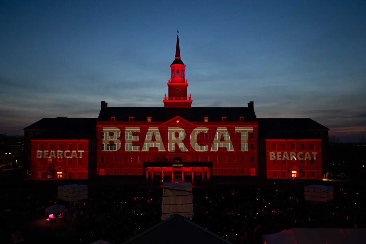 """The word """"Bearcat"""" projected on UC building at twilight"""