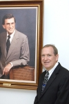 Dr. Dan Lucas posing next to a portrait of his father