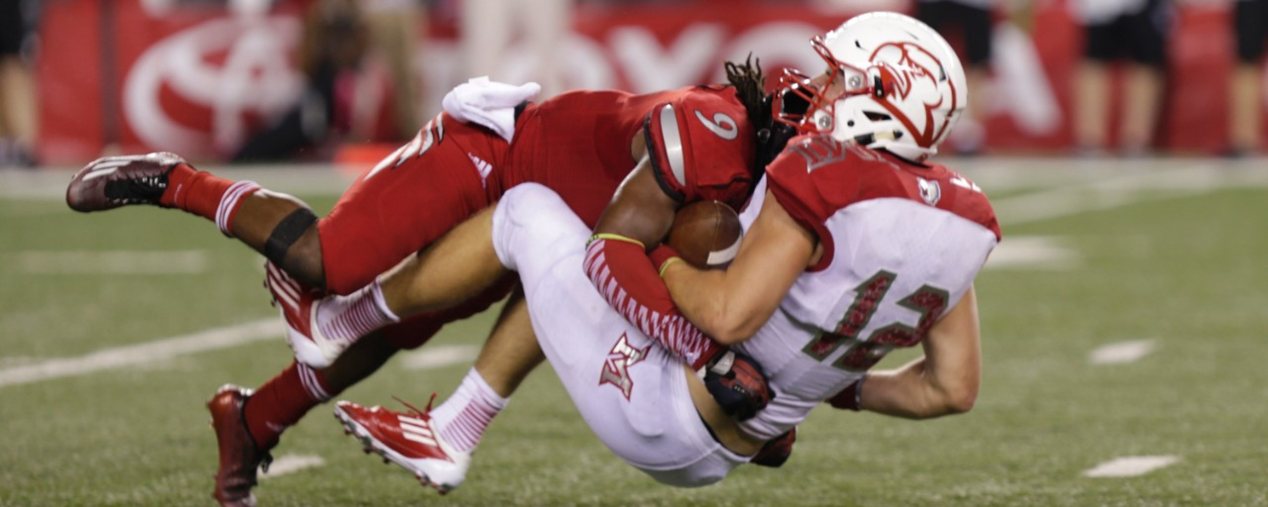Football player tackling quarterback.